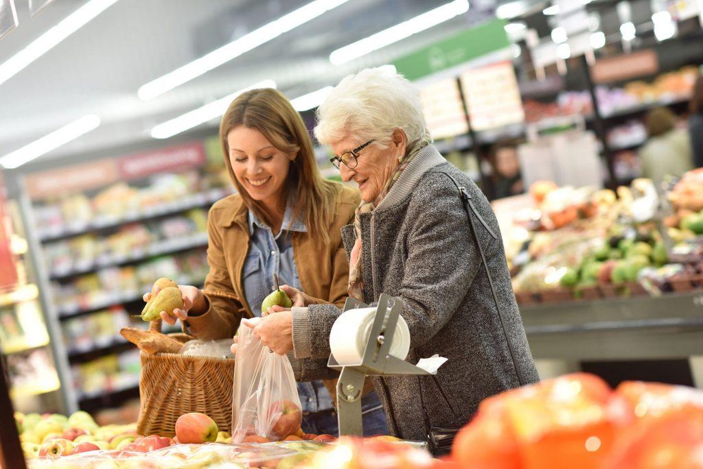 Mulher jovem com senhora idosa escolhem peras no mercado