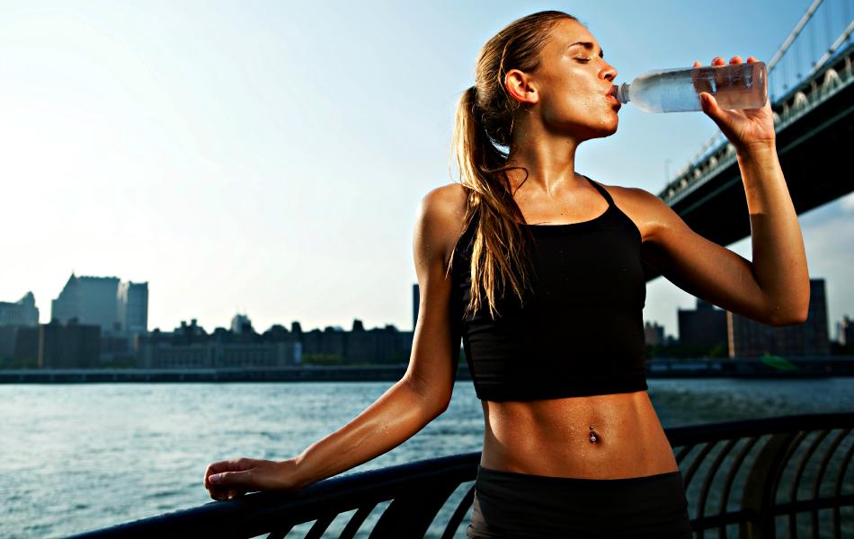 Mulher jovem bebe água após exercícios