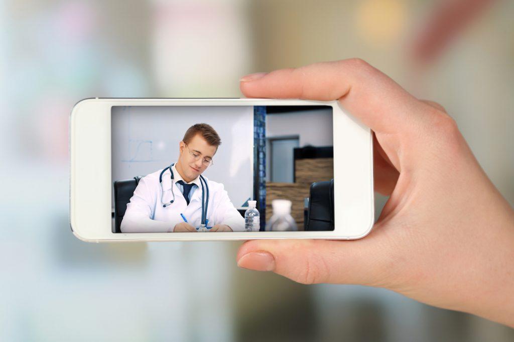 Paciente segura o aparelho celular, médico aparece na tela.