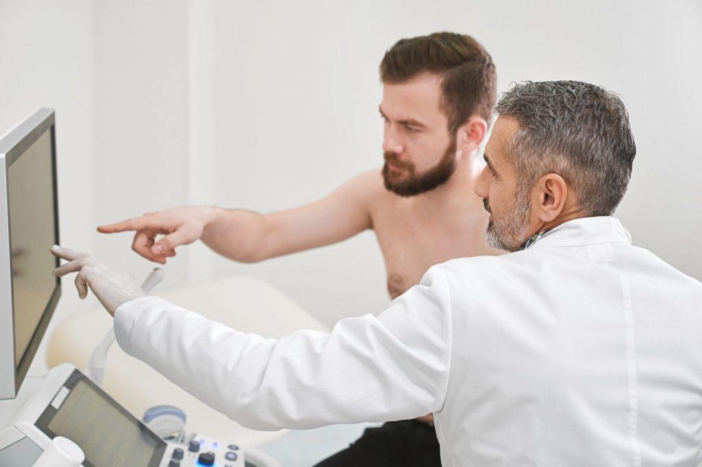 Médico e paciente observam exame de ultrassonografia e conversam
